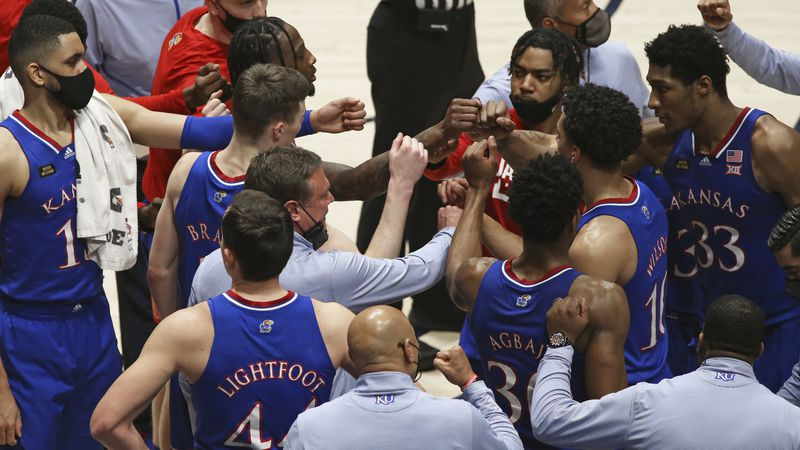 Kansas coach Bill Self meets with players during the second half of an NCAA college basketball...