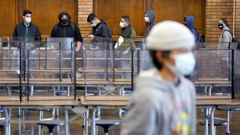 FILE - In this March 31, 2021, file photo, students wear masks as they wait in line for lunch...