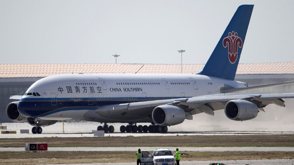 Airport crew watch from their car as a China Southern Airlines passenger jet lands during the...