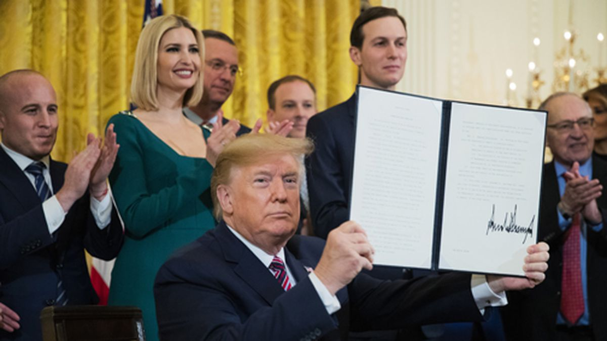 President Donald Trump shows the executive order he signed combating anti-Semitism in the U.S. during a Hanukkah reception in the East Room of the White House on Wednesday, Dec. 11, 2019, in Washington. (AP Photo/Manuel Balce Ceneta)