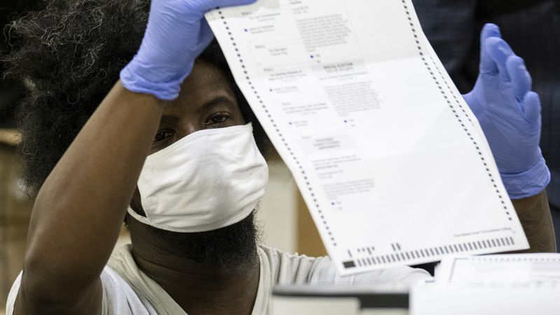 FILE - In this Nov. 25, 2020 file photo, workers scan ballots as the Fulton County presidential...
