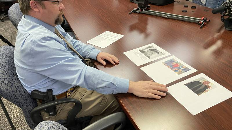 Detective Tim Relph with Wichita Police looks over pictures of Art Goebel as he asks the public...