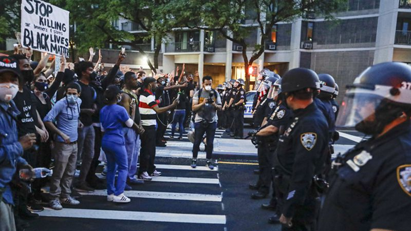 Protesters confront New York Police officers as part of a solidarity rally calling for justice...