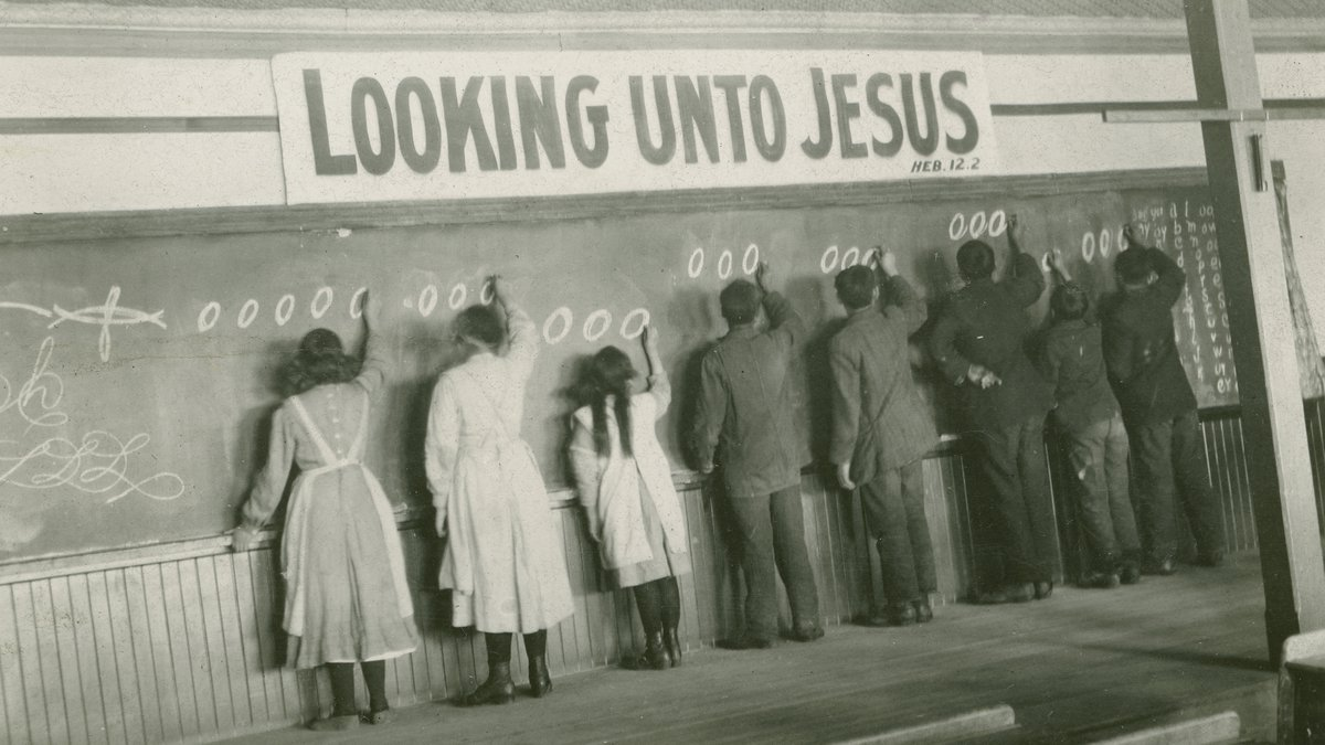 In this 1910s photo provided by the United Church of Canada Archives, students write on a...