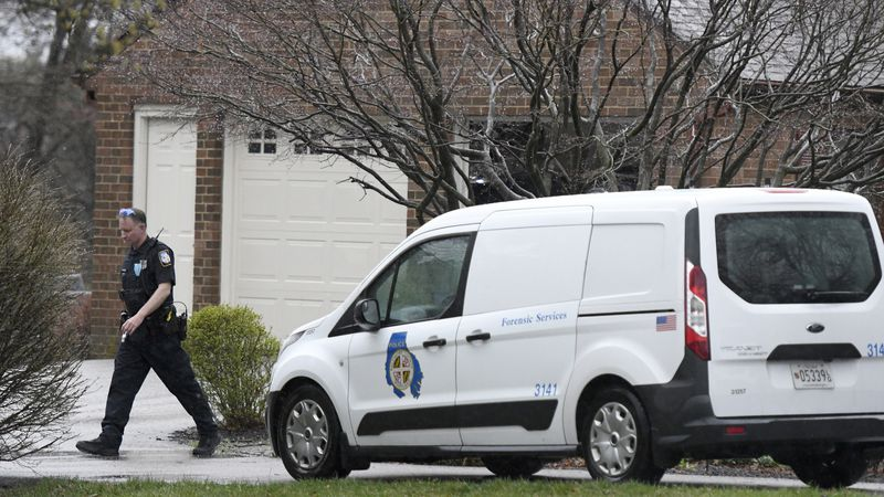 A police officer walks away from a home where at least two people were found dead in Baldwin,...