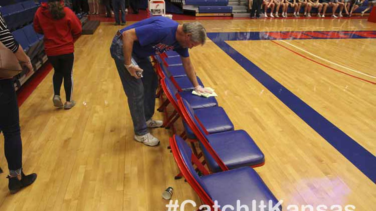 A member of the Hutchinson Community College maintenance department disinfects a team's bench during halftime. Teams compete in the Boys Quarterfinals of the 2020 KSHSAA Class 3A State Basketball Tournament held on Sam Butterfield Court at The Hutchinson Sports Arena on the campus of Hutchinson Community College in Hutchinson, Kansas on March 11, 2020.  (Photo: Joey Bahr, www.joeybahr.com)