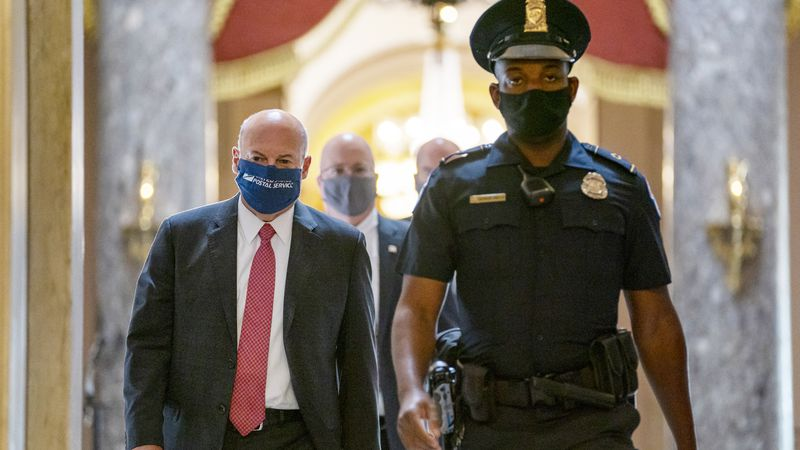 In this Aug. 5, 2020 file photo, Postmaster General Louis DeJoy, left, is escorted to House...