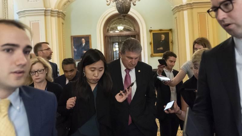Sen. Joe Manchin, D-W.Va., center walks to a meeting at the Capitol in Washington, Wednesday,...