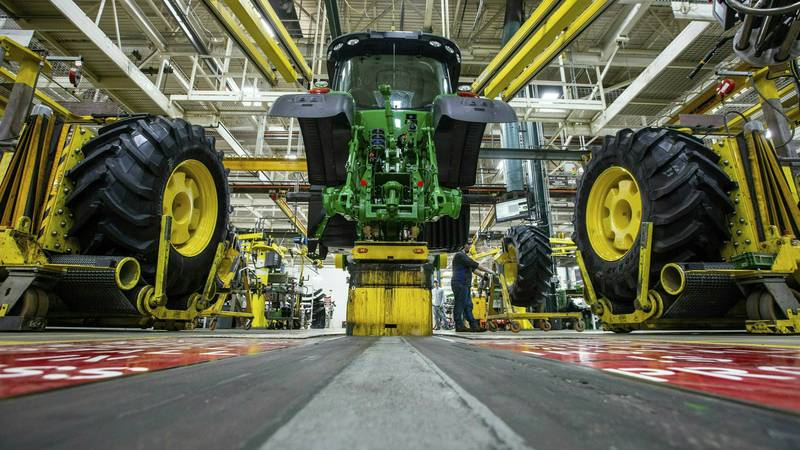 FILE - In this April 9, 2019 photo, wheels are attached as workers assemble a tractor at John...