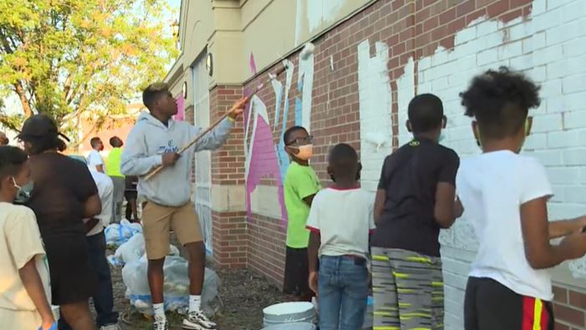 """Boys mentored through """"Real Men, Real Heroes,"""" work on mural at Wichita Public Library Maya..."""