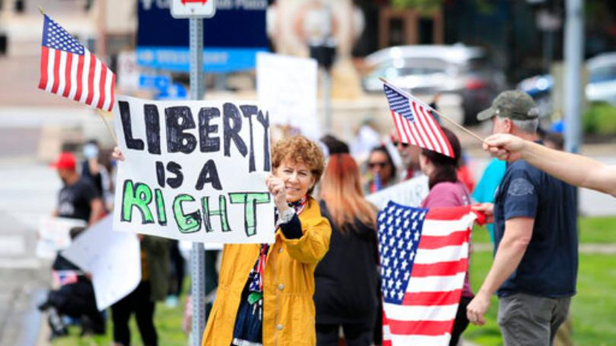 Protesters wanting the lifting of stay-at-home orders gather near the Country Club Plaza shopping area in Kansas City, Mo., Monday, April 20, 2020. (AP Photo/Orlin Wagner)