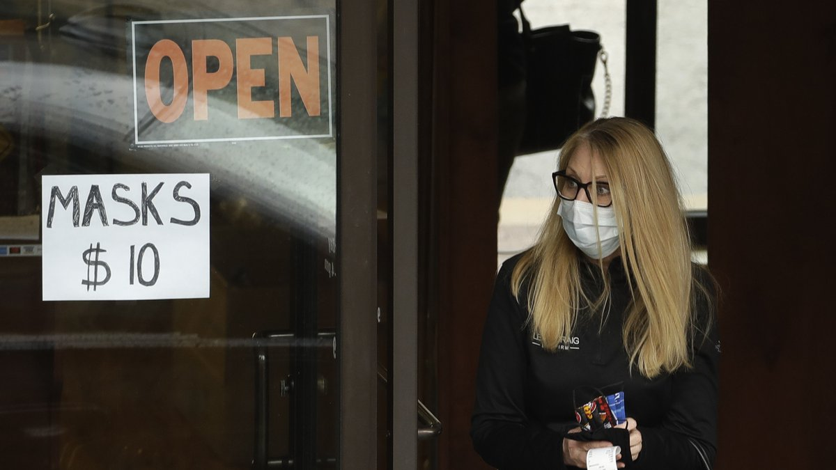A woman leaves a shop after purchasing face masks Thursday, May 7, 2020, in Kansas City, Mo....