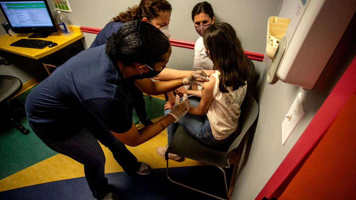 Middle school student Elise Robinson receives her first coronavirus vaccination on Wednesday,...
