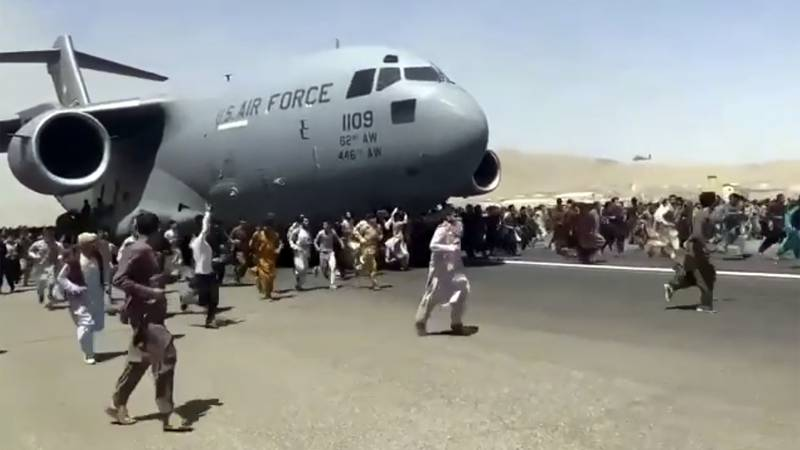 Hundreds of people run alongside a U.S. Air Force C-17 transport plane as it moves down a...