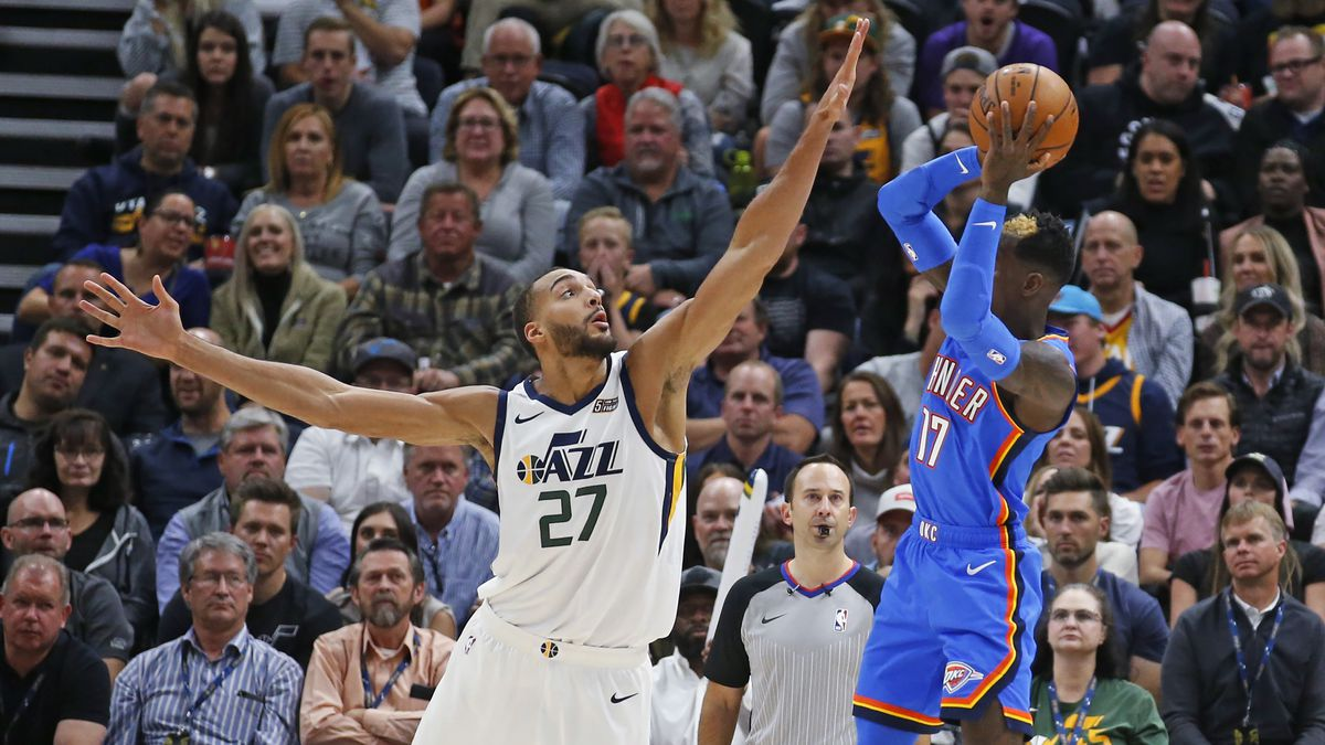 Utah Jazz center Rudy Gobert (27) defends against Oklahoma City Thunder guard Dennis Schroeder (17) during the second half of an NBA basketball game Wednesday, Oct. 23, 2019, in Salt Lake City. (AP Photo/Rick Bowmer)