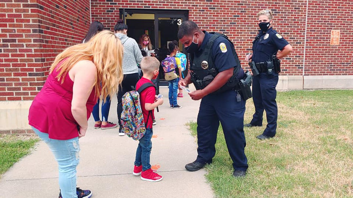 Wichita police officers hand out baseball cards and junior officer stickers to Wichita...