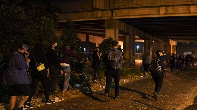 Protesters react to gunfire, Wednesday, Sept. 23, 2020, in Louisville, Ky. A police officer was...