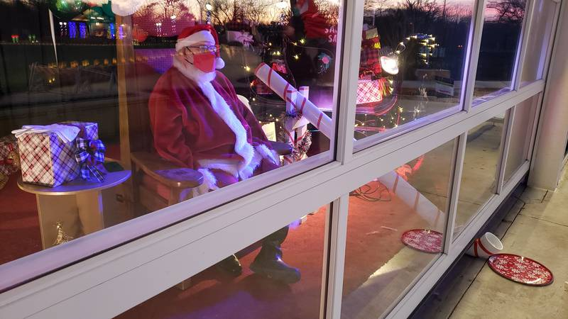 Santa Clause sites safely behind a glass door, waiting to greet children at Botanica.