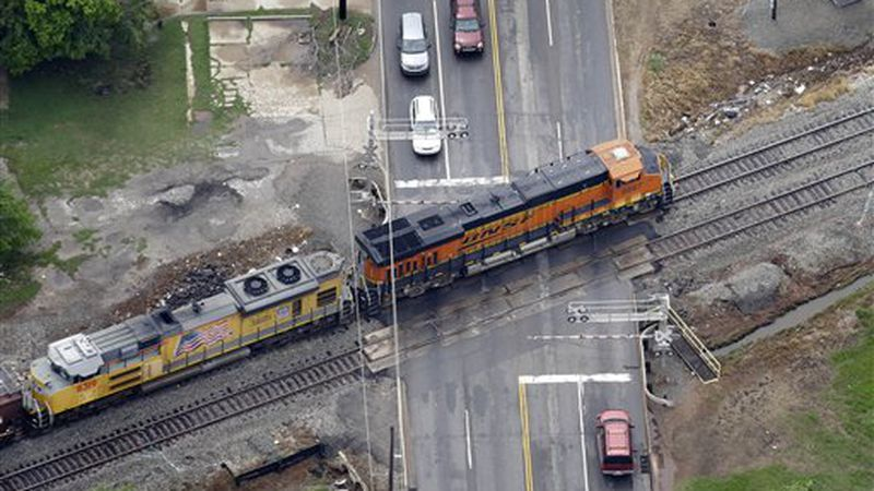 Burlington Northern Santa Fe locomotives make their by a rail road crossing Tuesday, May 21,...
