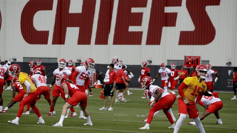 Kansas City Chiefs quarterback Patrick Mahomes (15) warms up with teammates during a workout at...