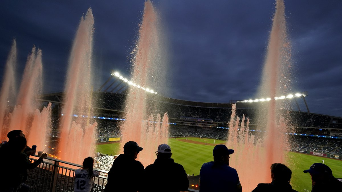 Fans watch from beyond the outfield fountains during the fifth inning of a baseball game...