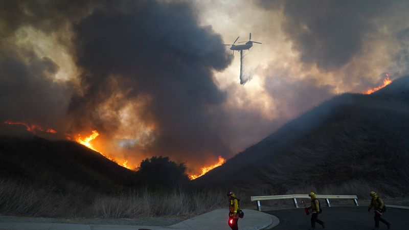 A helicopter drops water as firefighters walk with drip torches to set a backfire against the...