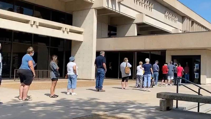 People lined up Wednesday outside the old library in downtown Wichita to get their third dose...