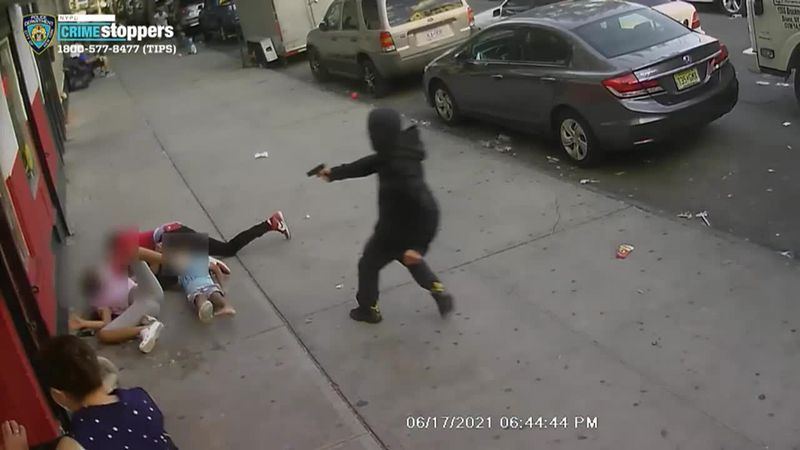 The NYPD is searching for suspects who shot a man who had fallen and knocked over two children.