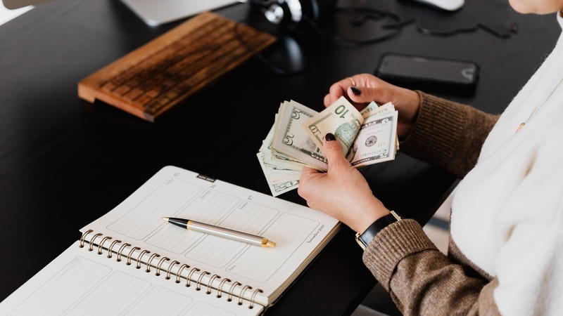 A woman counts her money while budgeting.