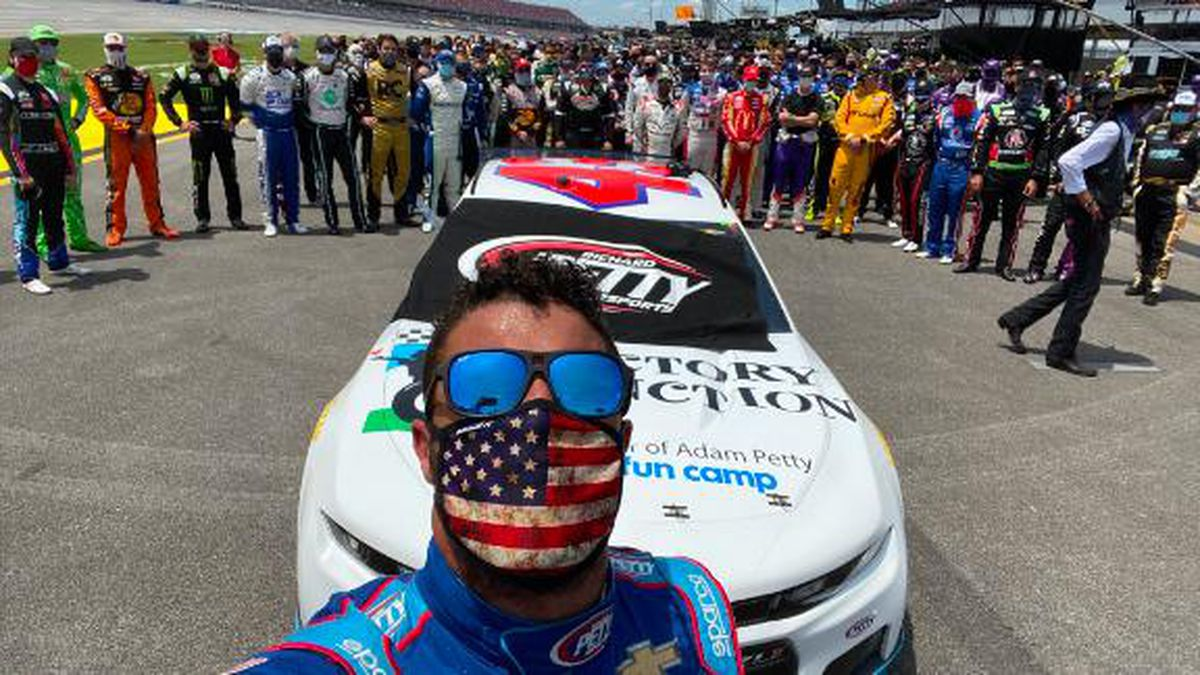 NASCAR drivers, pit crew members and others walked alongside Bubba Wallace and escorted his Number 43 car in a show of support a day after a noose was found in his garage. (CNN)