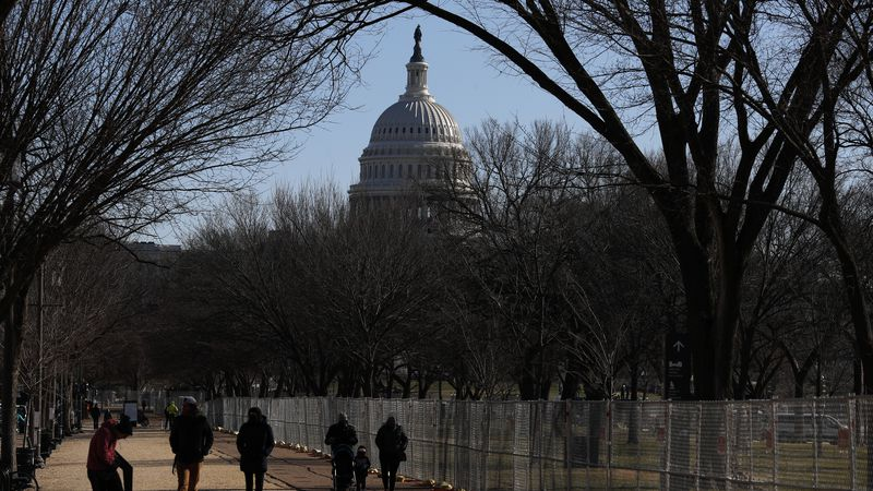 People stroll past a section of the National Mall by the Capitol where workers were still...