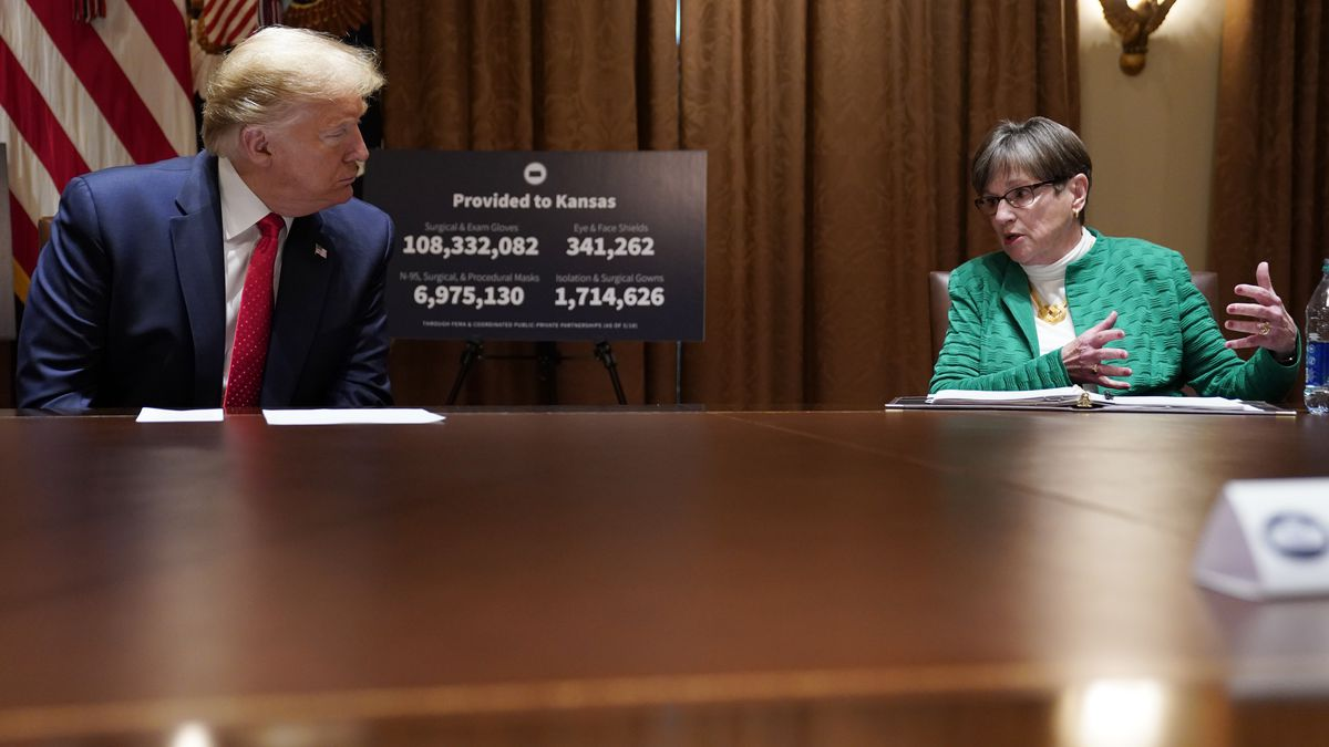 President Donald Trump listens during a meeting Kansas Gov. Laura Kelly, right, in the Cabinet Room of the White House, Wednesday, May 20, 2020, in Washington. (AP Photo/Evan Vucci)