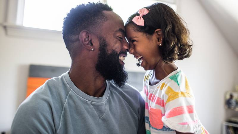 father and daughter laughing in bedroom - stock photo Credit: MoMo Productions/Getty Images