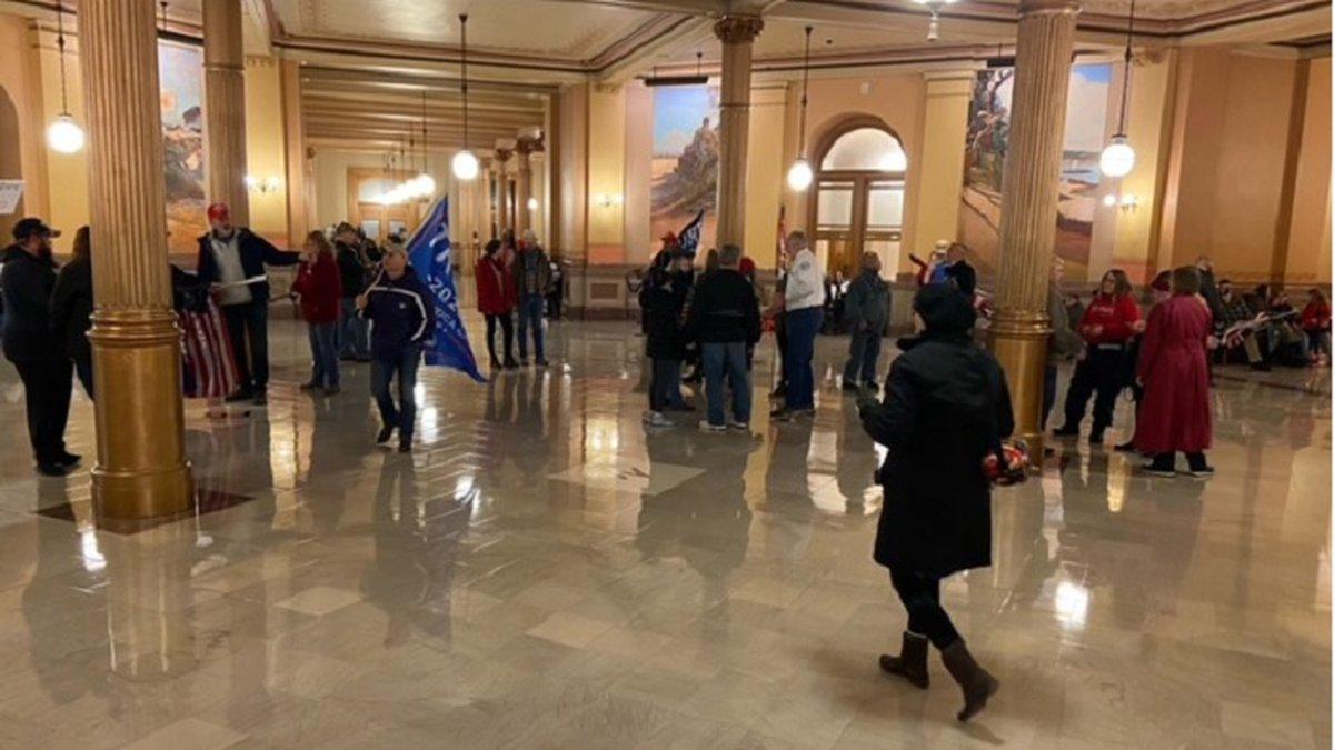 Pro-Donald Trump demonstrators mill around inside the Kansas Statehouse Jan. 6, 2021. Capitol...